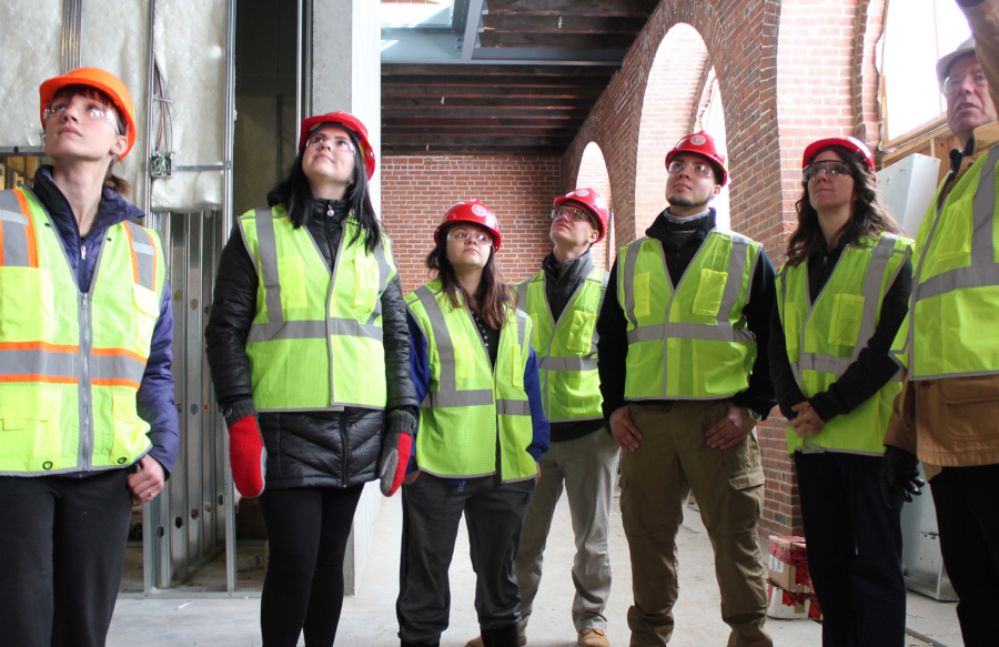 Students in hard hats and reflecting vests observing architecture