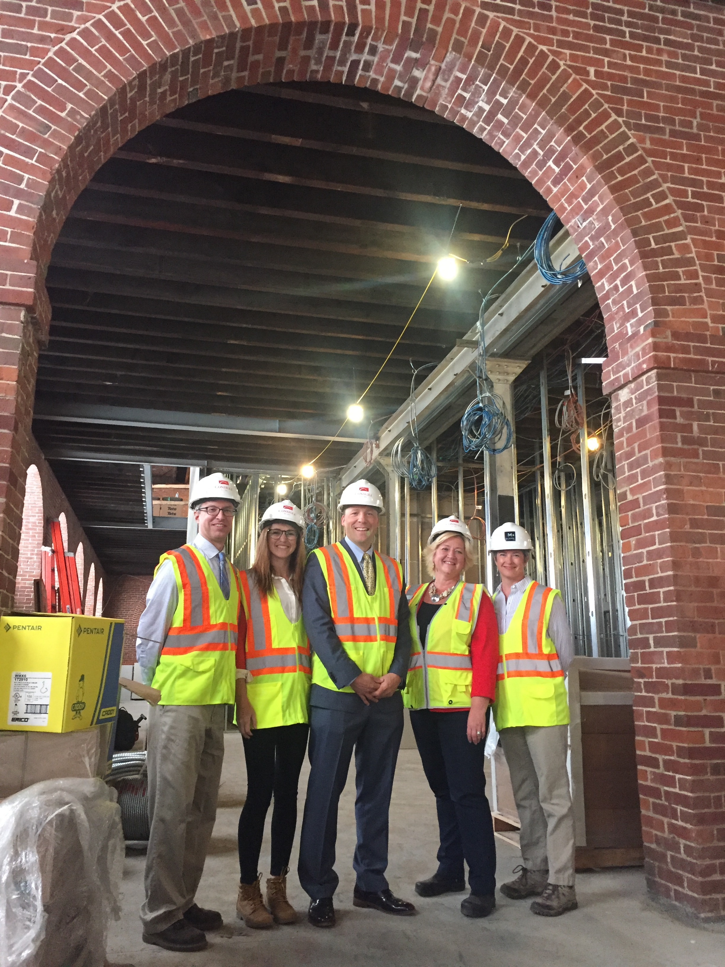 President Cook and others pose under an archway in Building 19