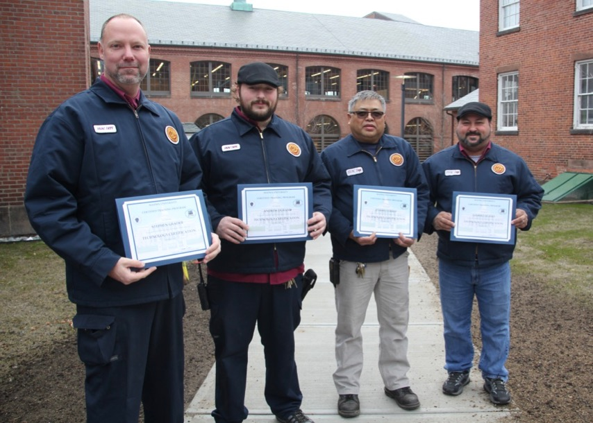 Four HVAC workers hold their certificates