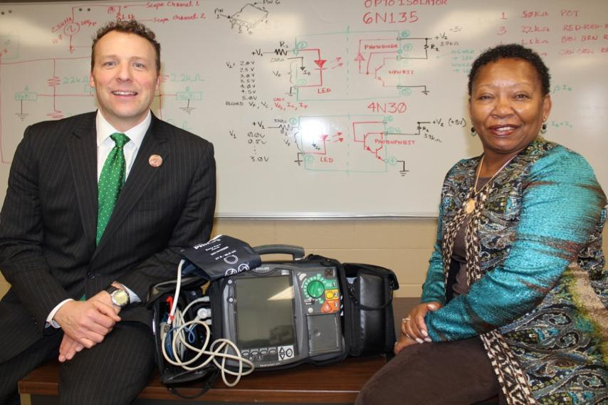 President Cook, Dean Smith with defibrillator