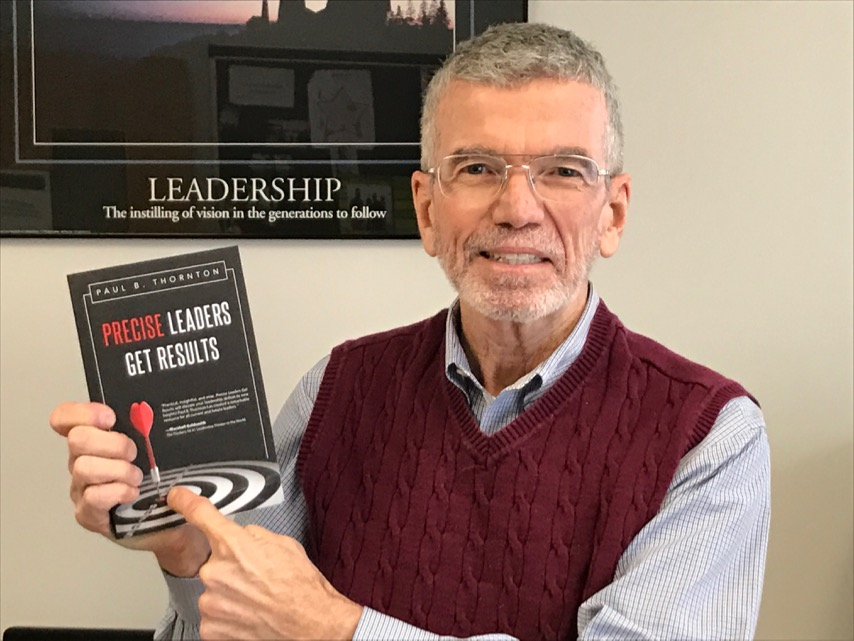 Professor Paul Thornton holds his book on leadership.